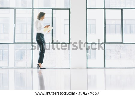 Photo business woman wearing modern suit, looking  mobile phone and holding papers in hands. Open space loft office. Panoramic windows background. Horizontal mockup.