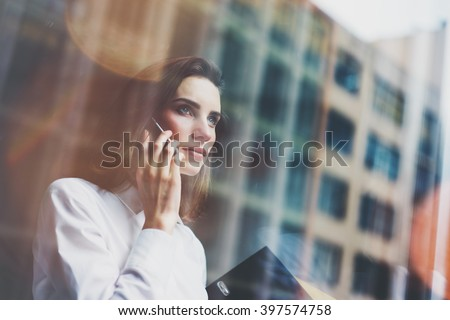 Photo business woman wearing modern white shirt, talking smartphone and holding documents in hands. Open space loft office. Panoramic windows background. Horizontal mockup. Film effect