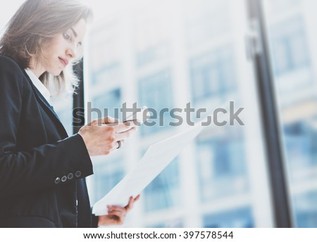 Photo business woman wearing suit, looking smartphone and holding documents in hands. Open space loft office. Panoramic windows background. Horizontal mockup. Film effect - stock photo