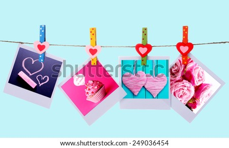 Photo cards hanging on the clothesline on blue background, Valentine's Day concept
