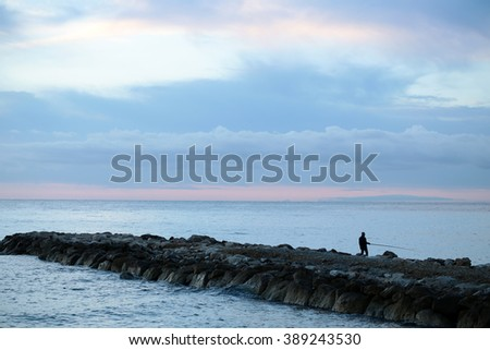 Photo closeup of beautiful calm evening marine with rocks one fisherman after amazing rose blue sunset and low cottony clouds on horizon on seascape background, horizontal picture - stock photo