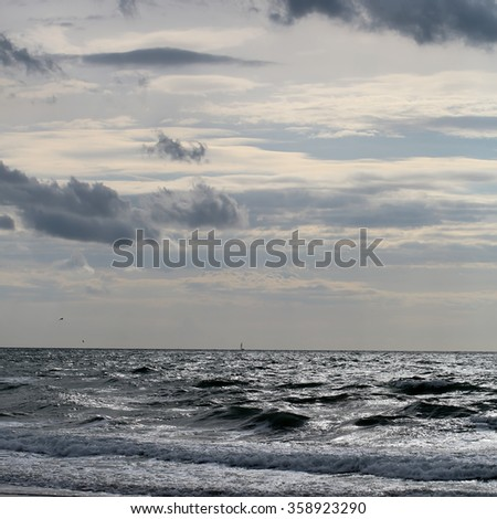 Photo closeup of beautiful clear dark grey sea ocean water surface with ripples low waves against cloudy sky on seascape background, square picture