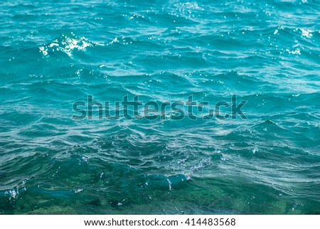 Photo closeup of beautiful clear turquoise sea ocean water surface with ripples low waves on seascape background, horizontal picture - stock photo