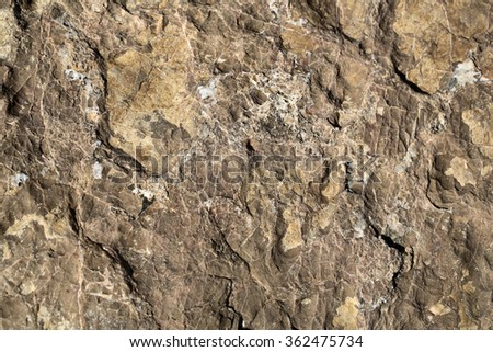 Photo closeup of costal beach sharp brown beige rock stone formations covered with salt minerals solid layer on natural background, horizontal picture