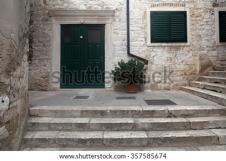 Photo closeup of old aged medieval building made of white stone masonry with green wooden door shutters and potted mandarin tree outside on cityscape background, horizontal picture  - stock photo