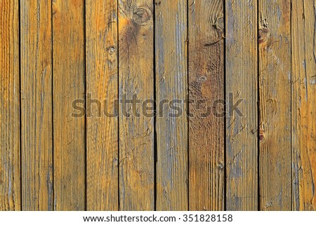 Photo closeup of old close boarded fence wooden palisade wood boards with knots loosing yellow paint on timber background, horizontal picture