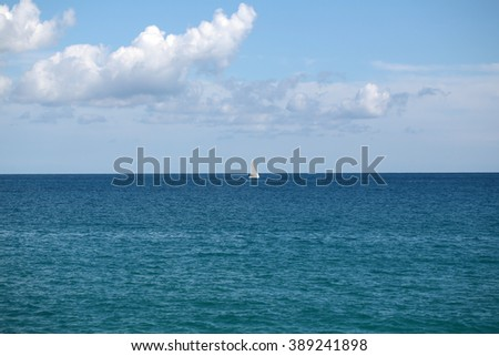 Photo closeup of one beautiful white sailing boat yacht offshore in calm blue sea silhouetted against cloudy sky day time on seascape background, horizontal picture