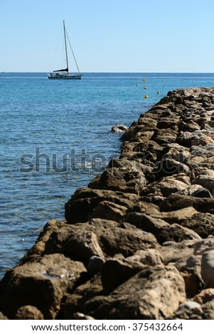 Photo closeup of stone pier coast and one classic yacht sailing boat vessel offshore in calm blue sea silhouetted against clear sky day time on beautiful seascape background, vertical picture - stock photo