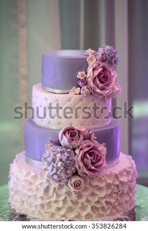 Photo closeup of traditional elegant delicious sweet four-layer wedding cake decorated with butter-cream roses on glass stand on blurred violet background, vertical picture  - stock photo
