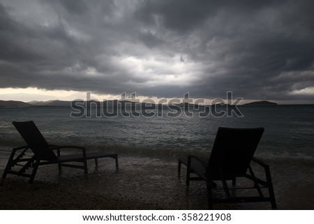 Photo closeup of two chaise lounges day beds standing on pebbles on beach at dusk low dark clouds bad weather grey sea shore against seascape background, horizontal picture - stock photo
