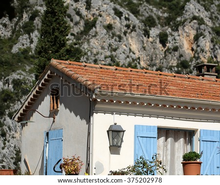 Photo closeup of white plastered facade of lovely small cottage farmhouse with open blue shutters and brown tiled roof on mountain scene background, horizontal picture - stock photo