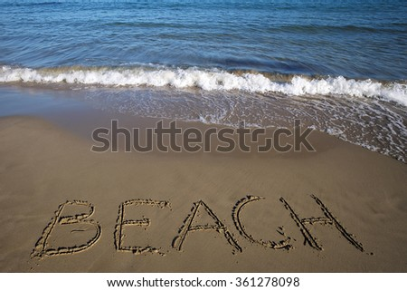 Photo closeup of word beach written on wet beige beach sea marine grained sand against blue waves with splashes white spindrifts running on seashore on seascape background, horizontal picture - stock photo