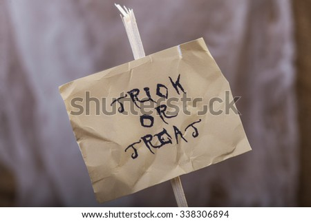 Photo closeup one hand-written happy Halloween lettering trick or treat phrase black letters on white creased paper sheet on stick over blurred sackcloth background, horizontal picture - stock photo