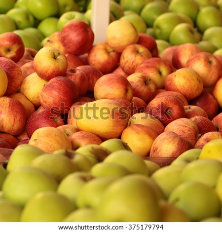 Photo closeup plastic lug-boxes full of clean organic natural fresh tasty ripe green red yellow apples fruit vitamin for healthy eating diet for sale on blurred background, square picture - stock photo