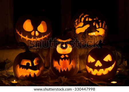 Photo composition from five pumpkins on Halloween. Jack, terrible hands, embittered, a Cyclops and evil pumpkin against an old window, leaves and candles. - stock photo