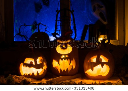 Photo composition from three pumpkins on Halloween. Embittered, Cyclop and frightened pumpkins against an old window, dry leaves and a terrible ghost in a window - stock photo