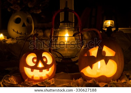Photo composition from two pumpkins on Halloween. Mad and scared pumpkins stand against an old window, leaves and candles. - stock photo