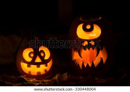 Photo composition from two pumpkins on Halloween. The madman and a Cyclops of pumpkin stand against an old window, leaves and candles. - stock photo