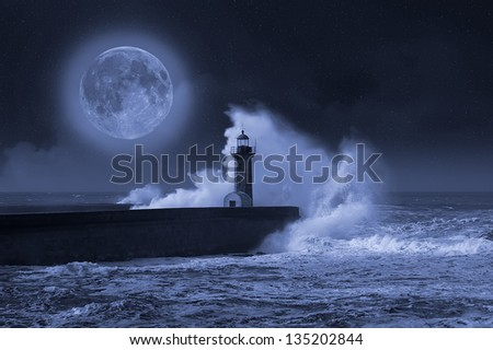 Photo composition of lighthouse with full moon. - stock photo