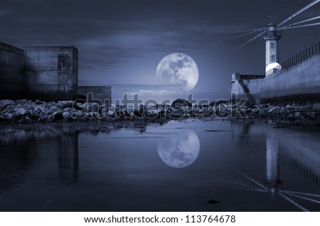 Photo composition of low tide view of lighthouse with full moon.