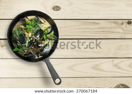 Photo. Copper pot of gourmet mussels served on a napkin garnished with fresh herbs for a tasty seafood meal - stock photo