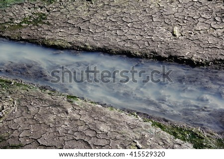 Photo detail of dry cracky clay ground with water stream - stock photo