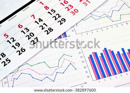 Photo diagrams and graphs on the paper with a monthly calendar - stock photo