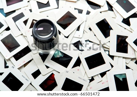 Photo editing magnifier loupe over stack of old transparency film slides in cardboard mount for a quality inspection (copyright holder and author is photographer)