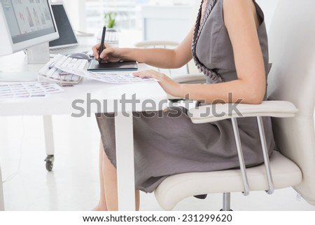 Photo editor working at her desk in creative office - stock photo