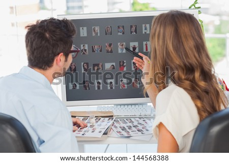 Photo editors working on thumbnails together in their office