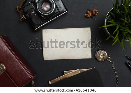 Photo empty on the vintage black table with camera and grass - stock photo