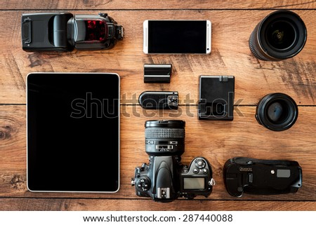 Photo equipment. Top view of diverse personal equipment for photographer laying on the wooden grain - stock photo