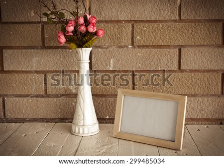 Photo frame and flowers on wooden table over wall background - Still life and vintage style - stock photo