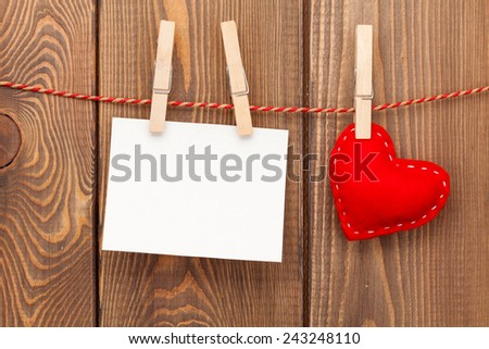 Photo frame and handmaded valentines day toy heart over wooden background - stock photo