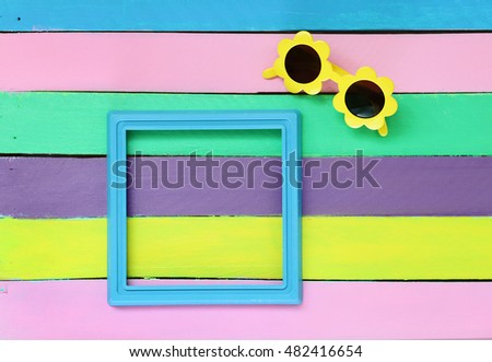 photo frame and sunglasses on colorful wooden background. Memories of summer