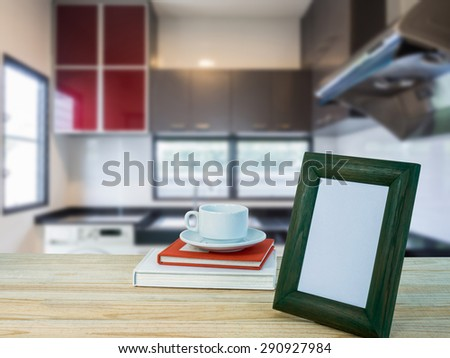 Photo frame, coffee cup on wooden counter top with modern kitchen blurry background - stock photo