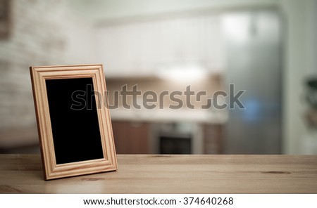 photo frame on the wooden table  in the kitchen - stock photo