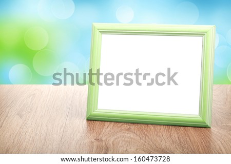 Photo frame on wood table over sunny day bokeh background - stock photo