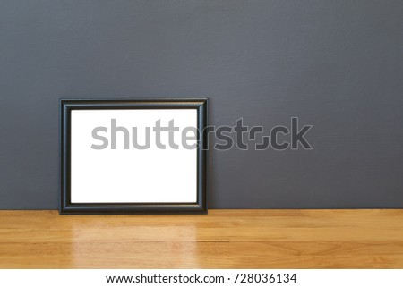 Photo frame on wooden table and cement wall background