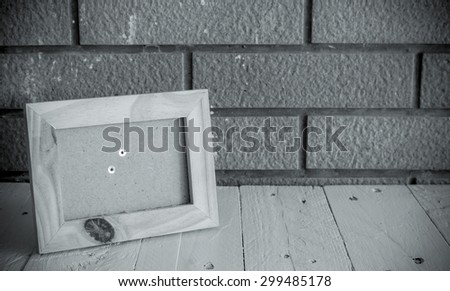 Photo frame on wooden table over wall background - Still life, black and white style
