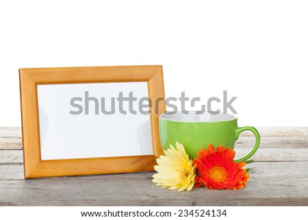 Photo frame on wooden table with cup of coffee and gerbera flowers - stock photo