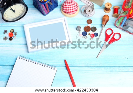 Photo frame tools tailor spools threads buttons needle sewing blue wooden background - stock photo