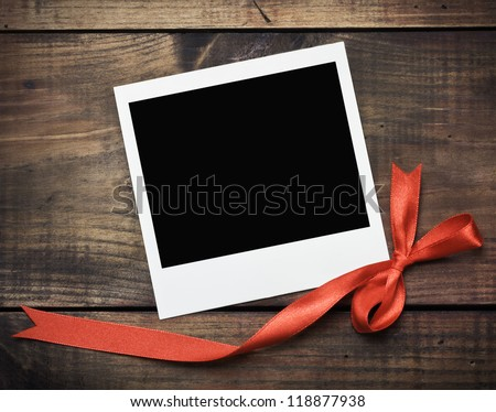 photo frame with a red bow on a wooden background - stock photo
