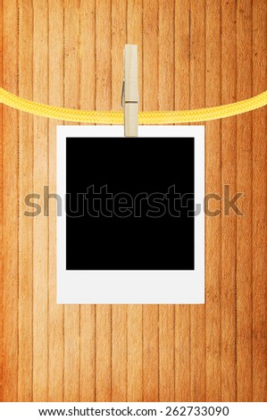photo frame with clothespin over wooden background - stock photo