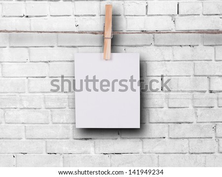 Photo frame with pins on rope over old aged brick wall - stock photo