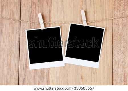 photo frame with space hanging on a rope. on wood background.