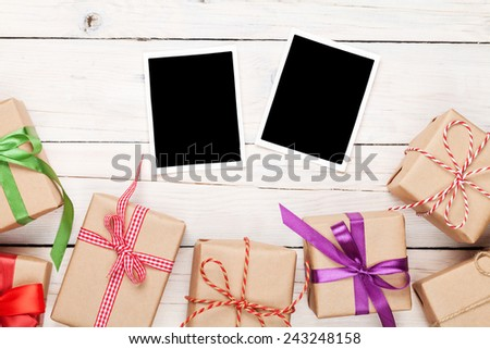 Photo frames and gift boxes with ribbons over white wooden table background - stock photo