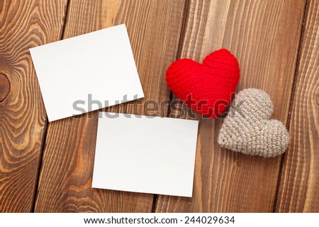 Photo frames and handmaded valentines day toy hearts over white wooden background - stock photo