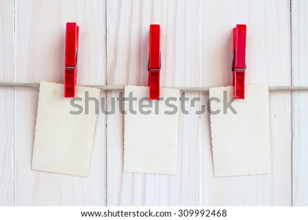 Photo frames hanging on a rope over white wooden background - stock photo
