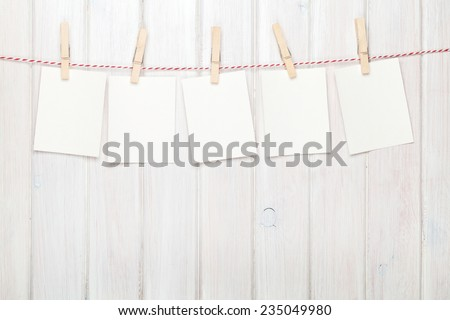 Photo frames hanging on rope over white wooden background - stock photo